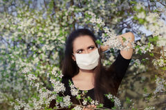Woman with Allergy with Respirator Mask in Spring Blooming Decor Royalty Free Stock Image