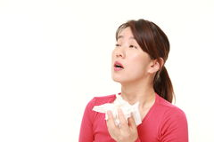 Woman with an allergy sneezing into tissue Stock Photo
