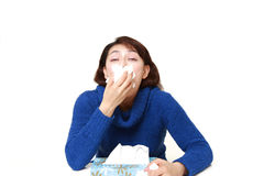 Woman with an allergy sneezing into tissue Stock Photography