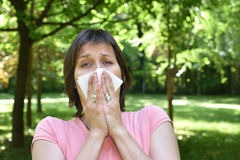 Woman with allergy symptom. Blowing her nose Royalty Free Stock Images