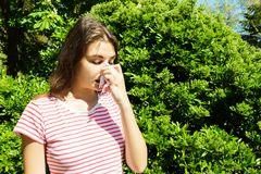 Woman with with allergy symptom blowing nose.  Royalty Free Stock Images