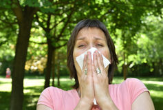 Woman with allergy symptom. Sneezing in a tissue Royalty Free Stock Photography