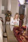 Woman alone at big table eating Stock Image