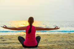 Woman alone does yoga at sunset Royalty Free Stock Photography