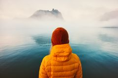 Woman alone looking at foggy cold sea traveling adventure lifestyle. Outdoor solitude emotions winter clothing hat and down jacket royalty free stock photo