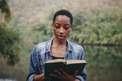Woman alone in nature reading a book. African American woman alone in nature reading a book leisure concept Royalty Free Stock Image