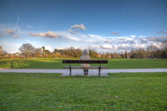 Woman alone on park bench Stock Photo
