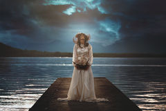 Woman alone on surreal lake pier Stock Images