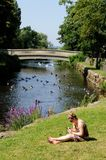 Woman alongside riverbank using mobile phone. Royalty Free Stock Image