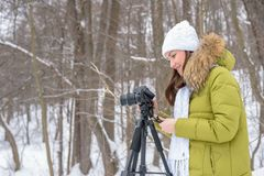 Woman Amateur photographer takes a winter landscape on the lake in the forest. copy space.  royalty free stock image