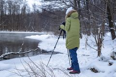 Woman Amateur photographer takes a winter landscape on the lake in the forest. copy space.  stock photos