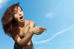 Woman amazed and pointing against the sky Stock Image