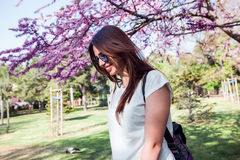 Woman on amazing blooming tree background.Stylish backpack,spring colors,brunette girl in a park,resting,white shirt,back portrait Stock Photo