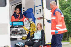 Woman in ambulance with paramedics aid accident. Woman in ambulance with emergency paramedics aid bike accident smiling royalty free stock image