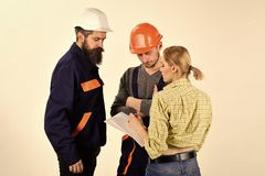 Woman amend plan of repair. Supervisor not satisfied with renovation. Misunderstanding concept. Brigade of workers. Builders in helmets, repairers, lady royalty free stock photo