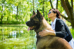 Woman with an American Akita dog. The woman is spending time with American Akita dog near the pond stock photo
