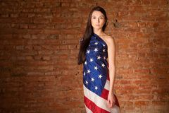 Woman in the American flag. On the background of a brick wall Stock Image