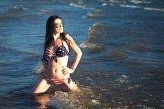 Woman in in american flag bikini in water, sea, waves. Fashion Stock Photo