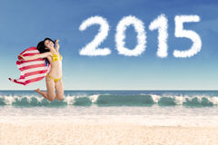 Woman with american flag in new year holiday. Attractive woman jumping on beach while holding american flag, enjoying new year holiday Royalty Free Stock Photo