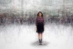 Woman amidst a busy crowd of moving people Royalty Free Stock Photos