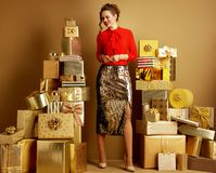 Free Woman Among 2 Piles Of Golden Gifts In Front Of Plain Wall Royalty Free Stock Image - 137222726
