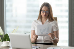 Woman analyzing downward financial indicators stock photography