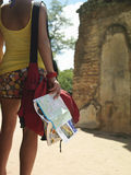 Woman By Ancient Ruins With Guidebook. Rear view midsection of a young woman looking at ancient ruins with guidebook in hand stock photo
