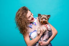 Woman And Dog In A Dress. Happy Woman With A Dog - Isolated Over A Green Background. Beautiful Young Woman Holding Small Dog. Stock Photos