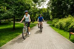 Free Woman And Man Riding Bicycles At Summer Green Park Stock Photography - 175316062