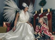 Woman with angel wings and boy . Woman with angel wings and  boy on a carpet near Christmas tree . Room with fireplace and Christmas decorations Royalty Free Stock Image