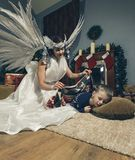 Woman with angel wings and sleeping boy . Woman with angel wings and sleeping boy on a carpet near Christmas tree .Room with fireplace and Christmas decorations Royalty Free Stock Photo