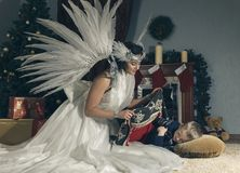 Woman with angel wings and sleeping boy . Woman with angel wings and sleeping boy on a carpet near Christmas tree .Room with fireplace and Christmas decorations Royalty Free Stock Photography