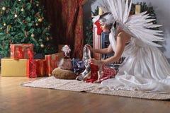 Sleeping boy near Christmas tree. Woman with angel wings and sleeping boy near Christmas tree.Conceptual Christmas image Stock Image