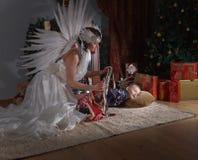Sleeping boy near Christmas tree. Woman with angel wings and sleeping boy near Christmas tree.Conceptual Christmas image Royalty Free Stock Photo