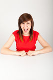 The woman is angrily sitting at the table Stock Photography