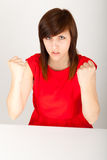 The woman is angrily sitting at the table Stock Images
