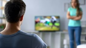 Woman angry because of guy watching sports competition, couple in conflict