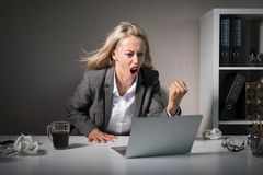 Woman angry at her laptop computer at work royalty free stock images