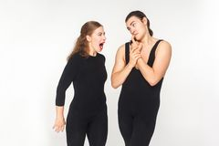 Woman angry and roar at man. Man have a funny look. Studio shot, isolated on white background stock photography