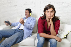 Woman  angry and upset while husband or boyfriend plays videogames ignoring her Stock Images
