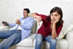 Woman  angry and upset while husband or boyfriend plays videogames ignoring her Royalty Free Stock Photos