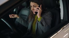 Woman is angry and upset on the steering wheel, because her car broke down. She is trying to get help by phone. Woman is angry, upset, beating her head on the stock footage