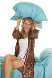 Woman in animal print robe blue sheets pillow over head Stock Photo