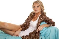 Woman animal print robe lay blue sheet looking serious Stock Photos