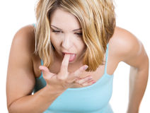 Woman: annoyed, frustrated and fed up sticking her finger in her throat showing she is about to throw up Stock Photos