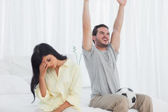 Woman annoyed at her partner watching football Stock Images