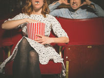 Woman annoying man in cinema by eating popcorn. A young women is eating popcorn loudly in a movie theater and is annoying the men sitting behind her royalty free stock photos