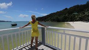 Woman at Anse Gouvernement. Slow motion: elegant tourist in yellow dress in tropical luxury destination. woman at balcony looking pristine beaches along the stock footage