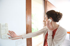 Woman answering door security phone Royalty Free Stock Image