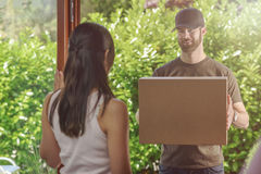 Woman answering the door to a deliveryman Royalty Free Stock Image